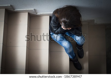 Depressed teenage girl with hands over face sitting on the stairs. - stock photo