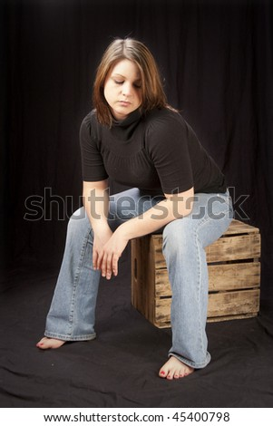 depressed teenaged girl seated on box - stock photo