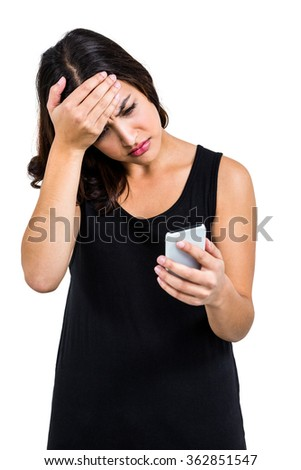 Depressed woman holding phone while standing against white background - stock photo