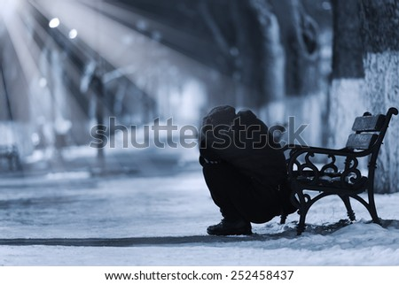 Depressed woman in front of a bench - stock photo