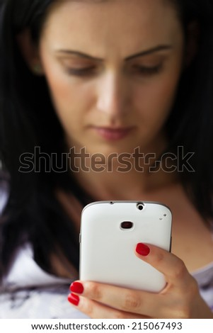 Depressed woman texting on white smartphone - stock photo
