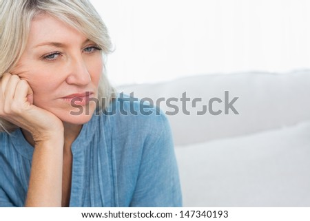 Depressed woman thinking at home on couch - stock photo