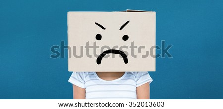 Depressed woman with box over head against blue background - stock photo