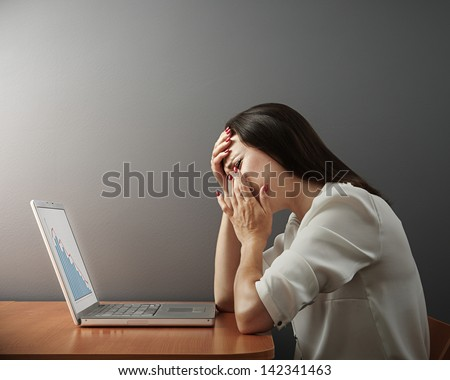 depressed woman with laptop over dark wall - stock photo