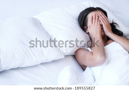 Depressed women in bed. Top view of young sad women lying on the bed and hiding her face in hands - stock photo