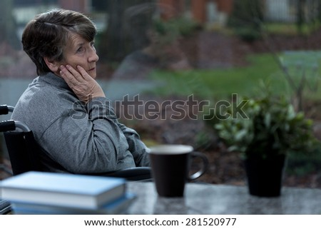 Depressed women sitting in a wheelchair at home - stock photo