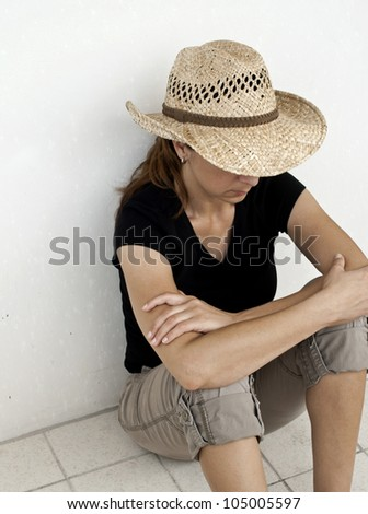 Depressed Women sitting on the tile floor with back against wall with straw hat outside with copy space. - stock photo