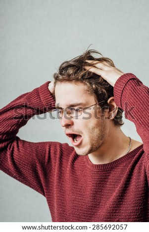 Depressed young business man holding his head - stock photo
