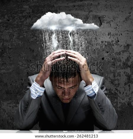 Depressed young businessman sitting wet under rain - stock photo