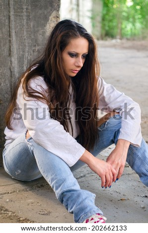 Depressed young girl sitting on the concrete floor of the abandoned building. - stock photo