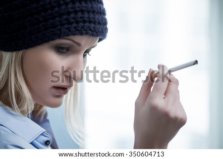 Depressed young woman is smoking cigarette. The druggie is standing near the window and looking down with frustration - stock photo
