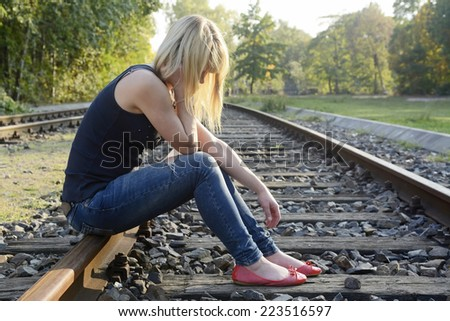depressed young woman sitting on rail track - stock photo