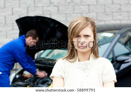 Depressed young woman standing in front of her car at the garage - stock photo