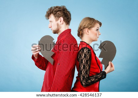 Depressing heartbreak relationship problems concept. Heartbroken couple standing together. Man with lady turned their backs holding broken heart. - stock photo
