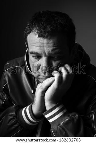 Depression: black and white portrait of a sad man - stock photo