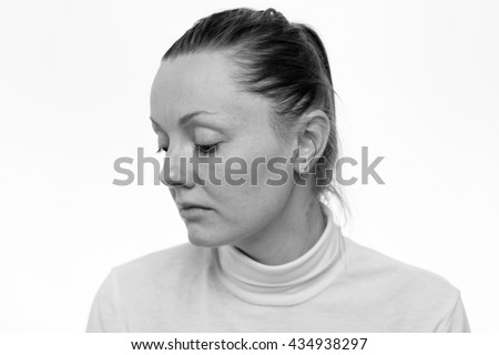 Depression. Close up portrait of a sad woman looking down, profile view, isolated on white background,  black and white - stock photo