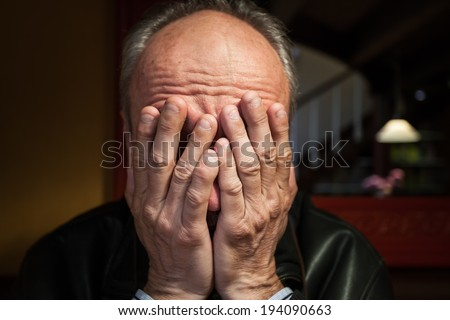 Depression. Elderly man sitting in the cafe. Covers his face by hand - stock photo