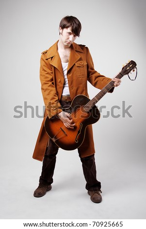 depressive musician and guitarist in a raincoat - stock photo