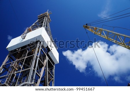 Derick of jack up drilling rig with the rig crane on sunny day - stock photo