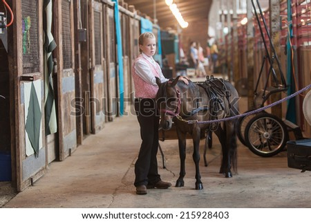 DES MOINES, IA /USA - AUGUST 10: Unidentified girl with minitature horse at Iowa State Fair on August 10, 2014 in Des Moines, Iowa, USA. - stock photo