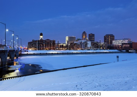 Des Moines skyline across frozen river. Des Moines, Iowa, USA. - stock photo