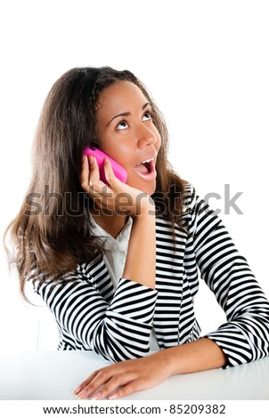 Description Teenage girl on a pink cell phone listening and looking shocked at a desk - stock photo