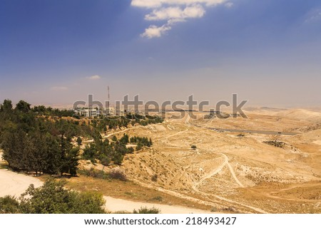 Desert area of West Bank and palestinian towns and villages behind the West Bank separation wall in the background, Israel, Middle east. View from the East Jerusalem, Mt. Scopus - stock photo