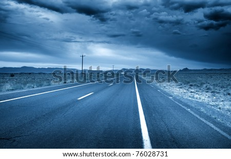 Desert drive with stormy sky in blue color - stock photo