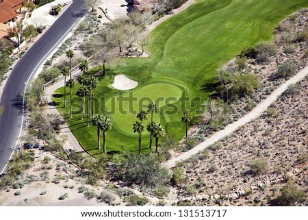 Desert Golf Course Hole with Palm Trees and Sand Trap - stock photo