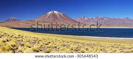 Desert lake Laguna Miscanti and Miscanti volcano in the Altiplano of Chile on a sunny day. - stock photo