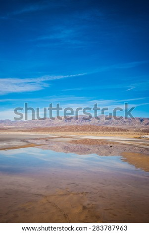 Desert landscape reflected in the waters of a pond formed in Death Valley National Park. - stock photo