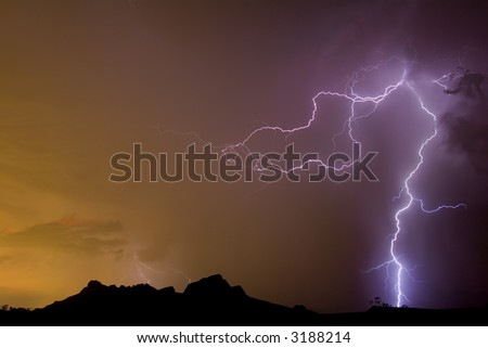 Desert lightning with storm picking up glow of city lights - stock photo
