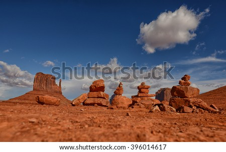 Desert meditation and line of prayer rocks or cairns near famous Monument Valley desert landmark  - stock photo