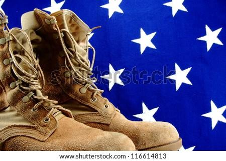 Desert military boots set against a vintage vivid cloth American flag - stock photo