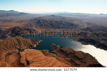 Desert mountains surrounding a cool blue lake. - stock photo
