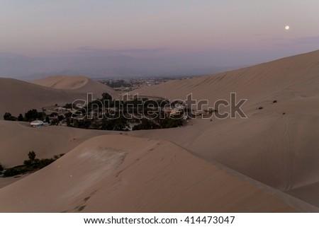 Desert oasis Huacachina near Ica, Peru. Moon visible. - stock photo