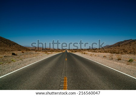 desert road highway with blue sky in background in death valley national park - stock photo