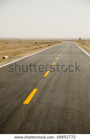 Desert road in Jiayuguan Pass, China, the west starting point of the whole Great Wall of China, on the Silk Route. - stock photo