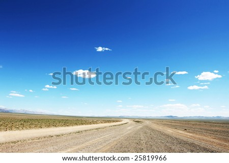 Desert road  in Mongolia with dramatic sky - stock photo