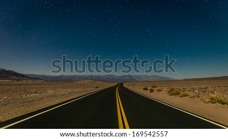 Desert road in the Death Valley by night - stock photo
