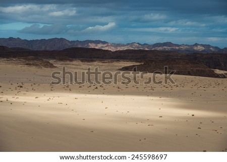Desert sands, mountains and cloudy blue sky - stock photo