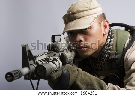desert storm soldier in the army dressed in camo aiming for shot - stock photo