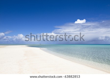 Desert white sand beach front of a turquoise lagoon - stock photo