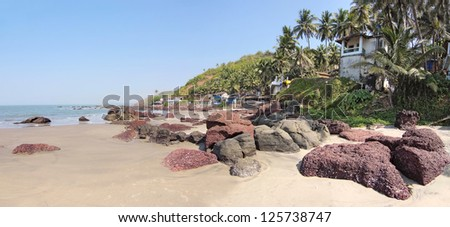 deserted beach with huts in Goa, India - stock photo