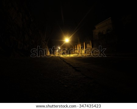Deserted night street/alley in Lviv. Ground viewpoint. Dark, quiet and mysterious atmosphere. Bright yellow lamp in the frame center, dark borders with high walls and paving. - stock photo
