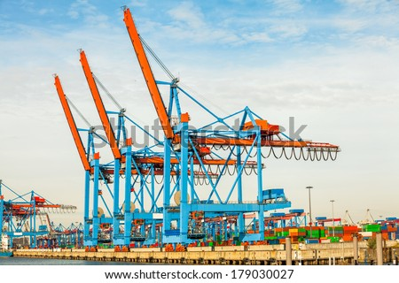 Deserted port terminal in a harbour for loading and offloading cargo ships and freight with rows of large industrial cranes to lift goods off the decks and from the holds - stock photo