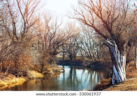 Deserted river and riverbank in late autumn - stock photo