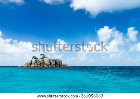 Deserted rocky island in the ocean. Covered with sparse vegetation and trees. The Seychelles. - stock photo