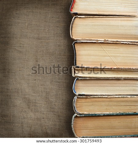 Design concept of wisdom and knowledge power - close up view on stacked old books placed on dimmed fabric canvas natural linen texture background. Clipping path included - stock photo