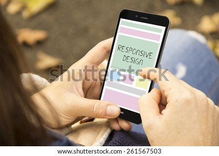 design concept: young woman with responsive design phone at the park - stock photo